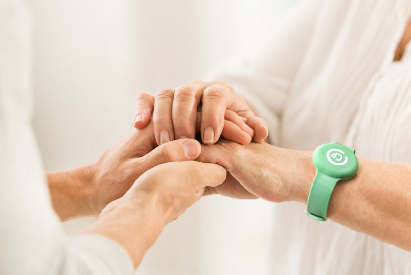 elderly woman holding hands with daughter and wearing a smart health wristband pouchpass