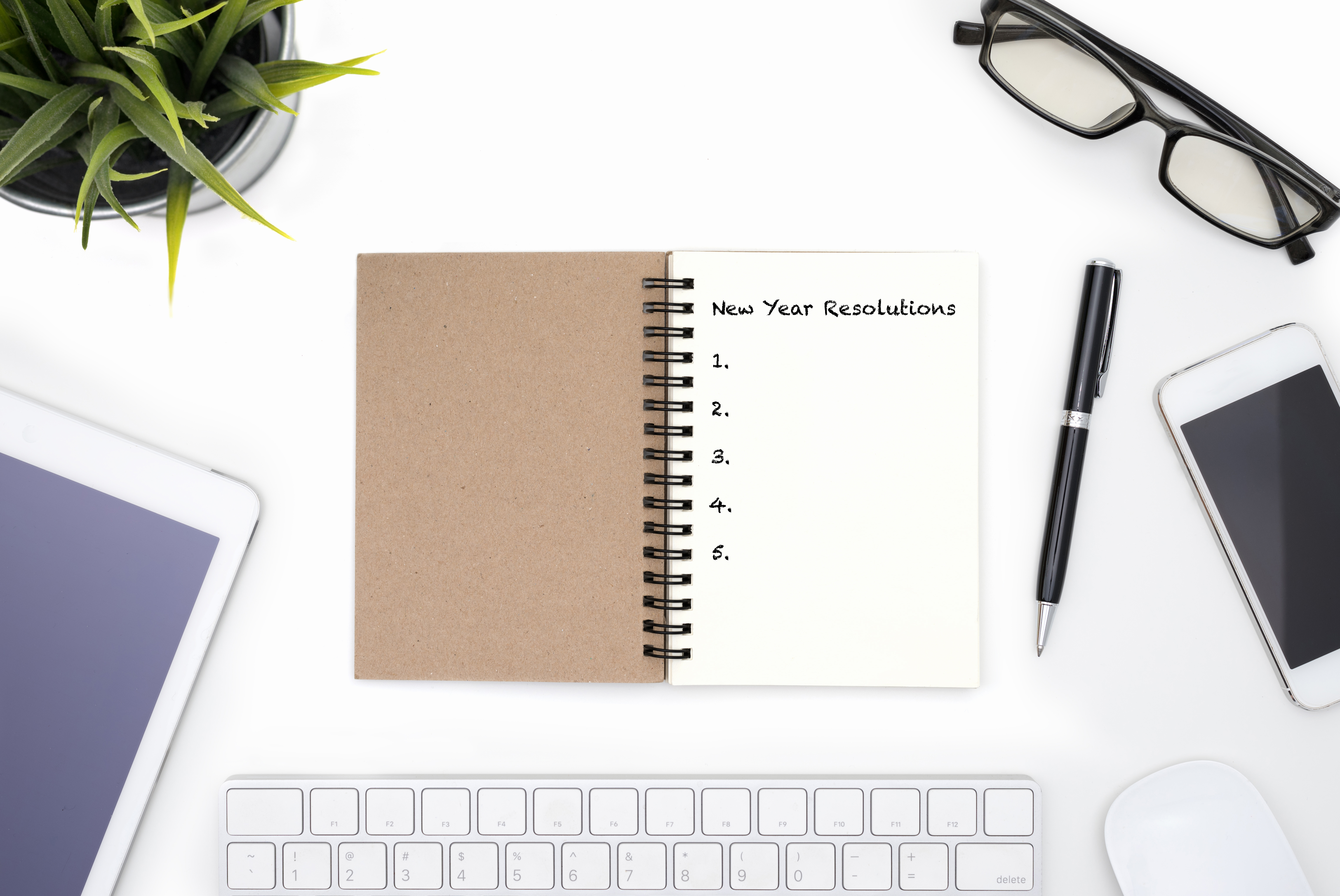 new year's resolution 2021 pouchpass  New year resolutions concept with open notebook, pen, mobile phone, tablet, small plant and eye glasses on white desk