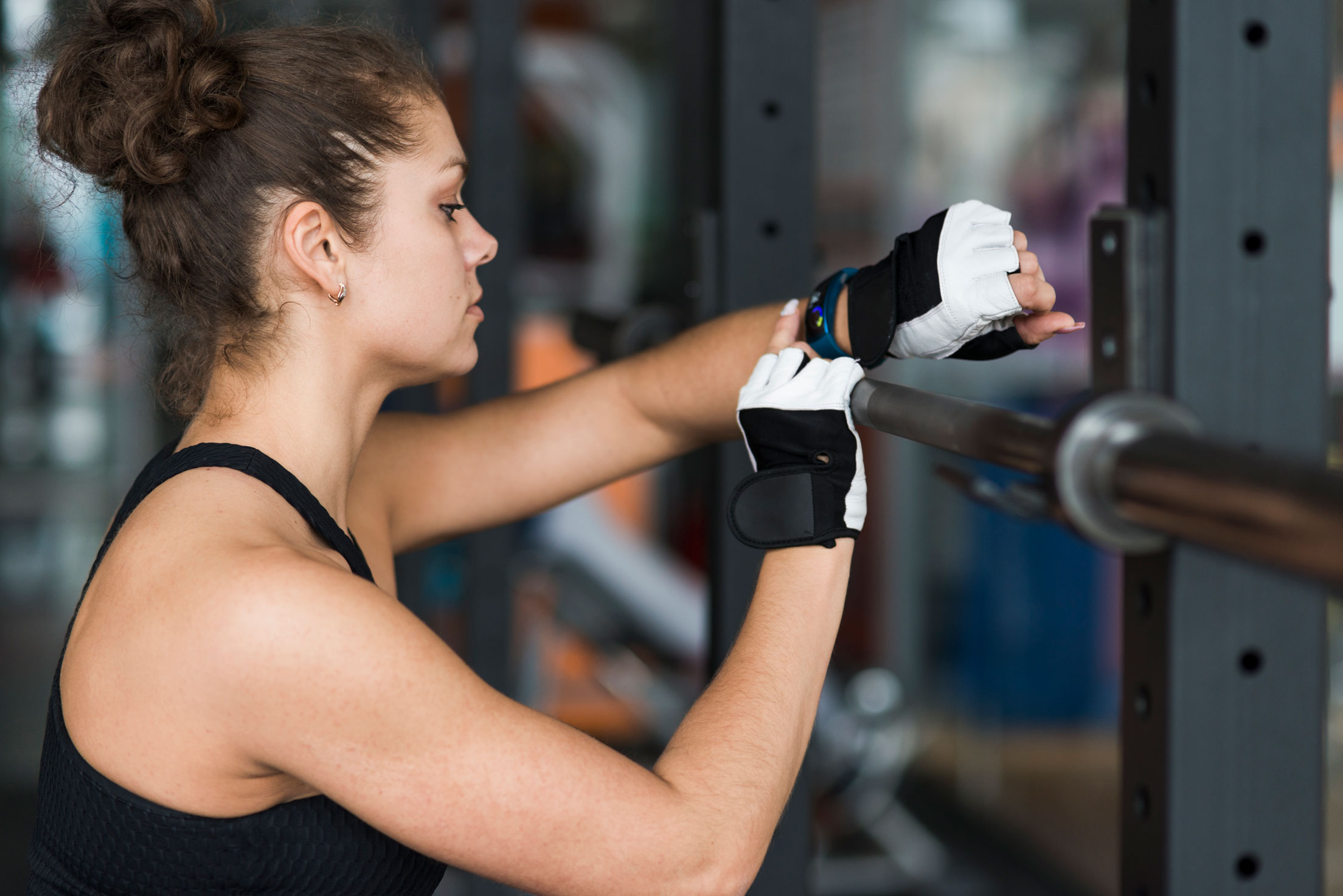 woman working out at the gym while checking her smart health wristband pouchpass