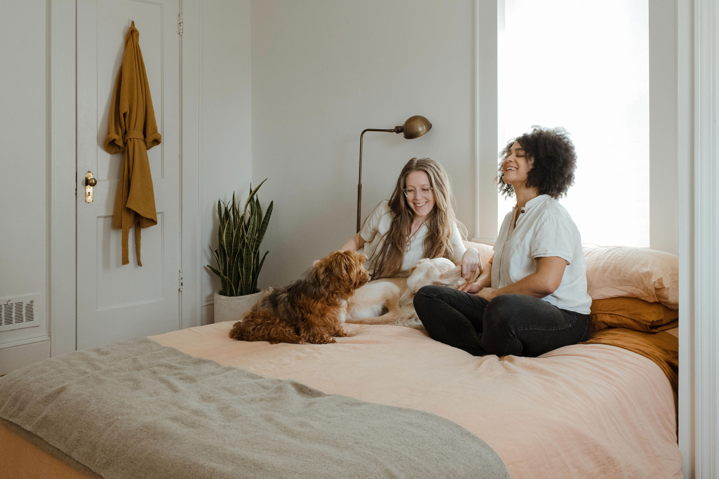two women chatting with their dog laughing