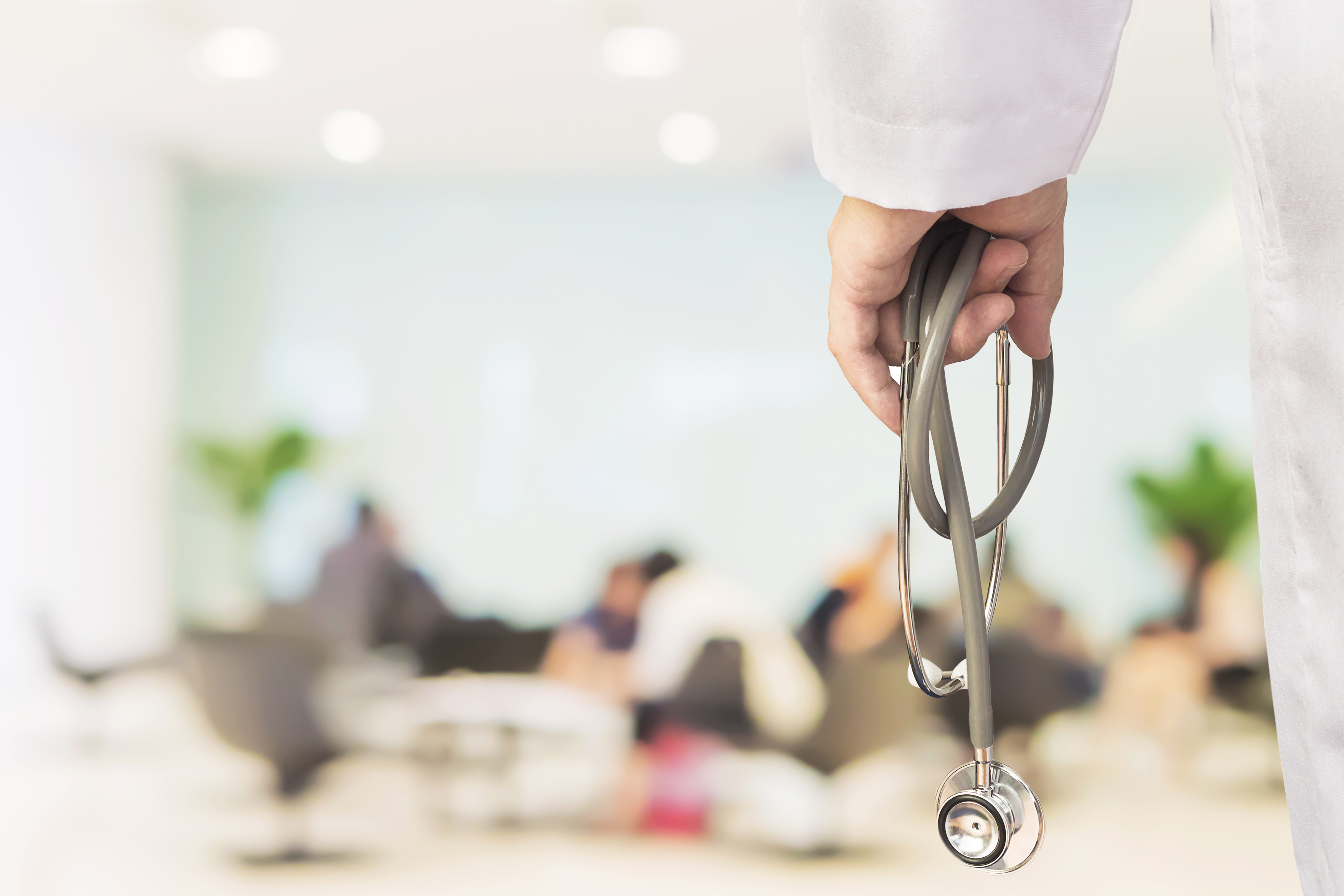 Doctor is going to examine his patient using his stethoscope over sitting people in modern hospital background