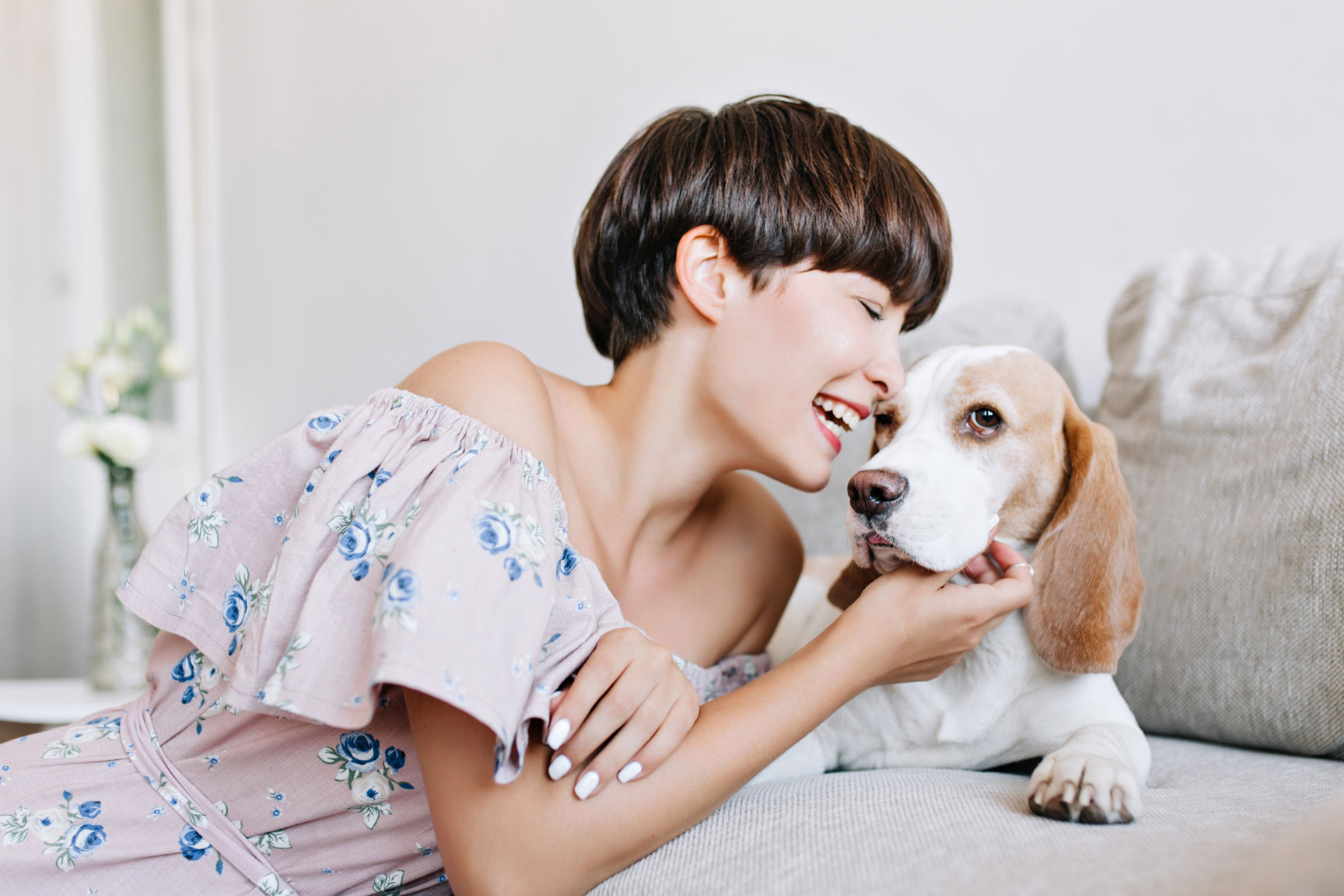 woman laughing with her dog kissing the dog