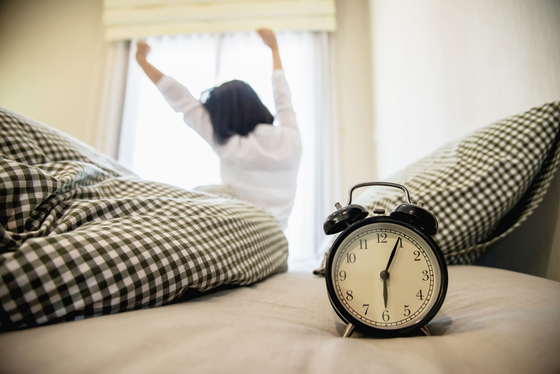 woman waking up early with alarm clock and stretching