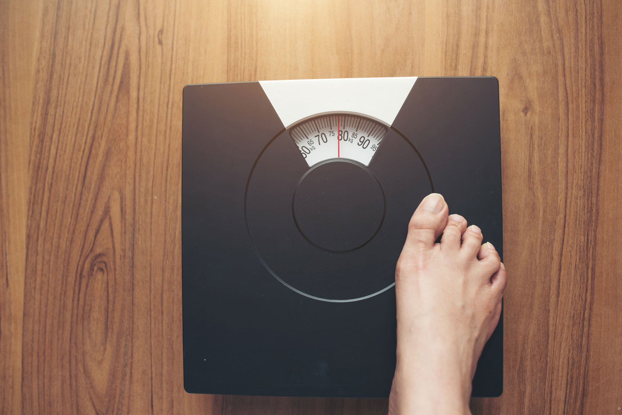 woman feet standing on weighing scale diet