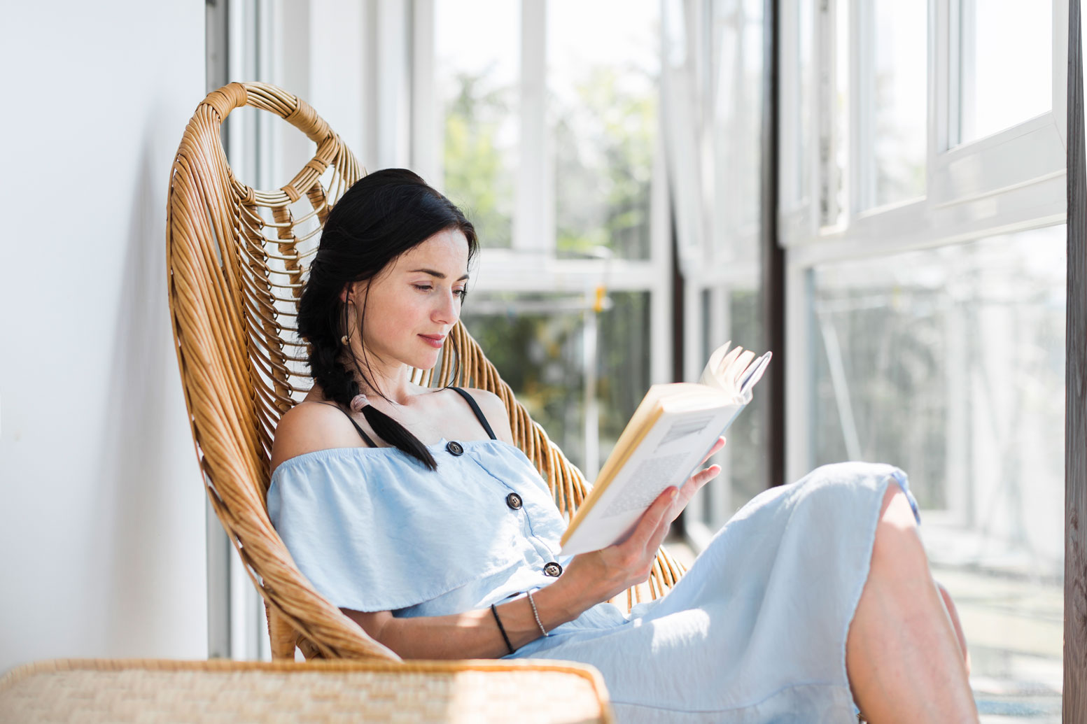 young woman reading a book outside sitting in a chair
