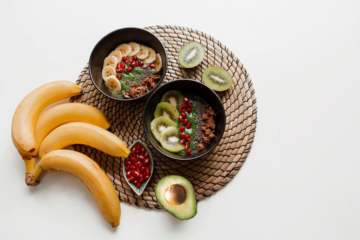 overhead view of a plate with vegan food bananas avocados kiwi pomegranate seeds and granola