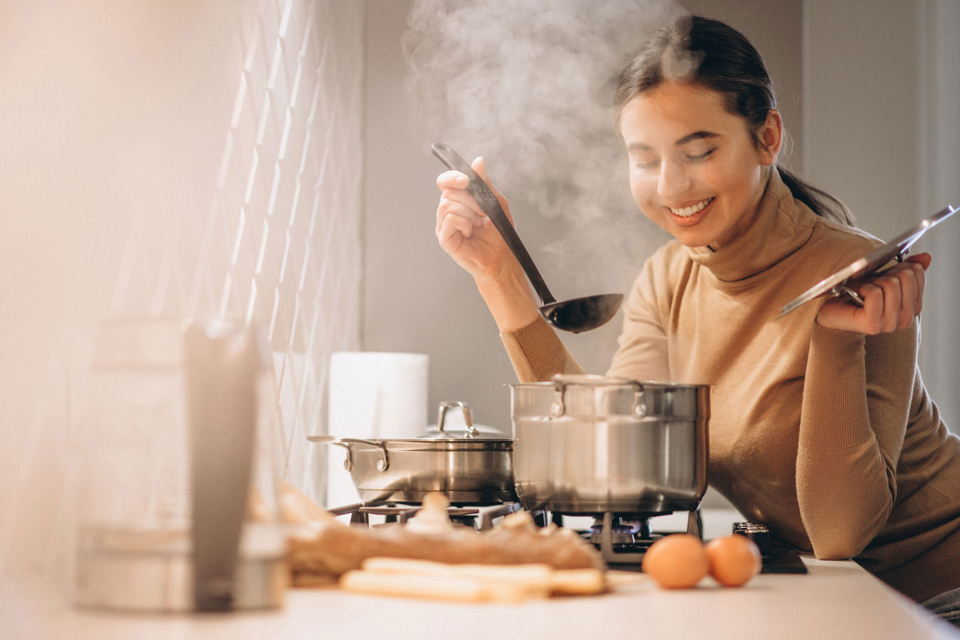 woman cooking in the kitchen while smiling with steam coming out of the pot