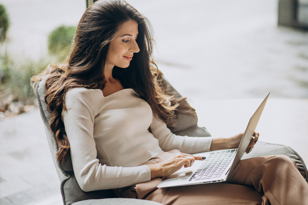 young woman business empire on a laptop outside sitting