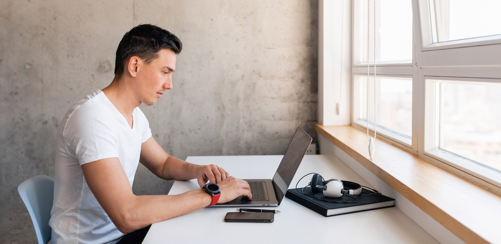 young handsome smiling man casual outfil sitting on a table working with a laptop
