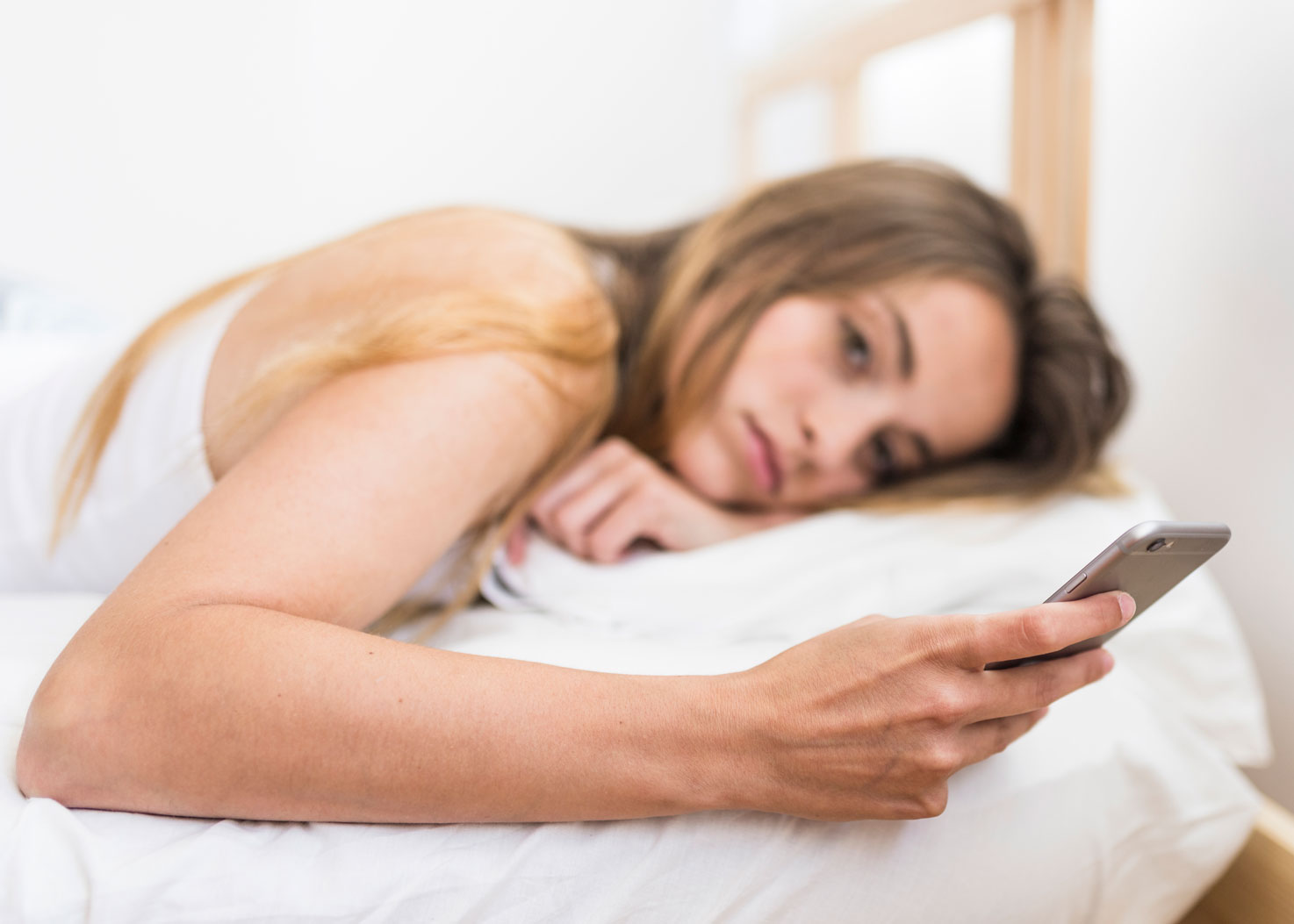 young woman lying in bed texting checking her phone
